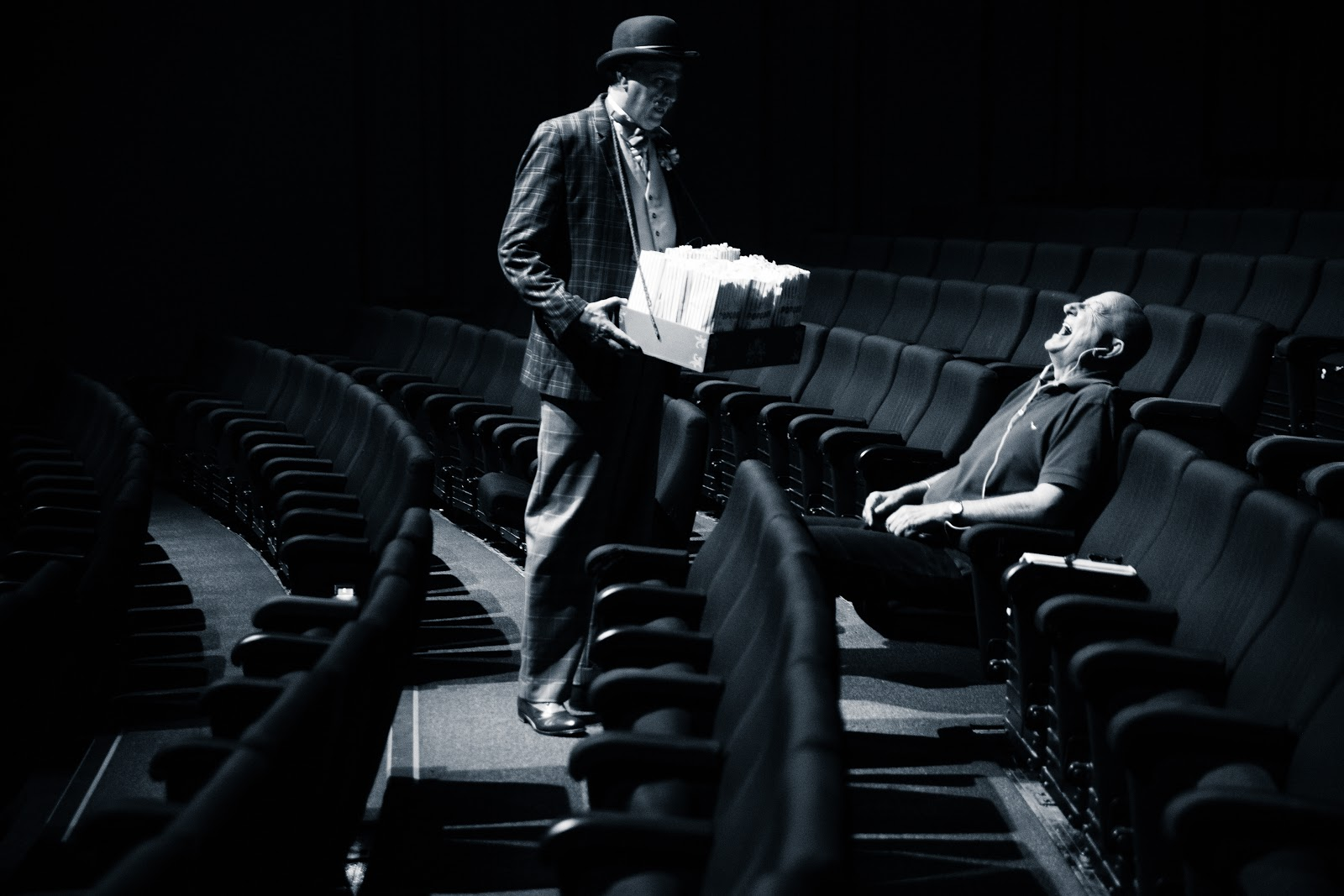 In an almost empty theater, a popcorn man (the clown of the shows) stands in front of an audience member, who is throwing his head back in laughter at something the popcorn man did.