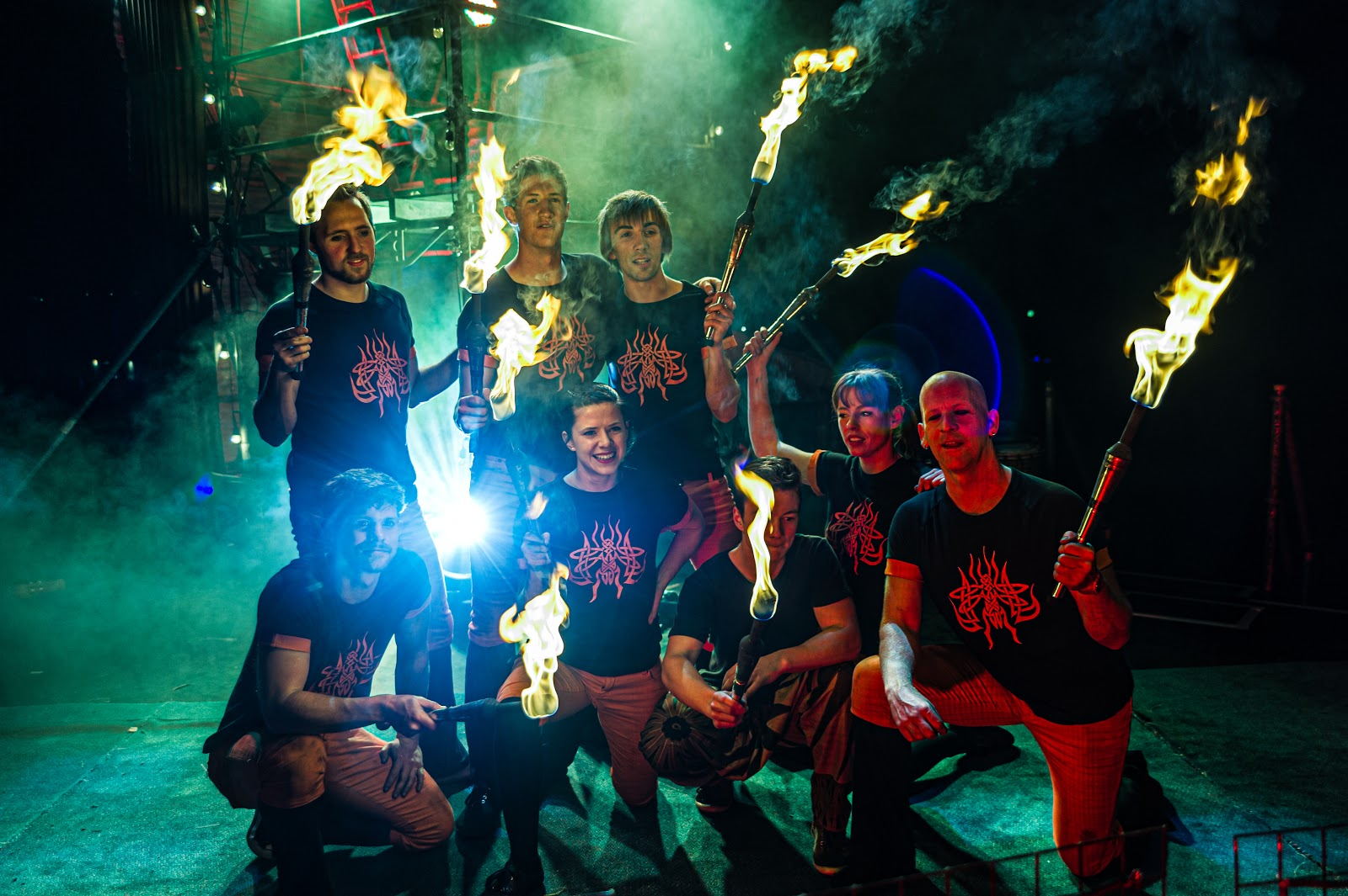 A group of 8 fire spinners poses on a dark stage with their fire implements.