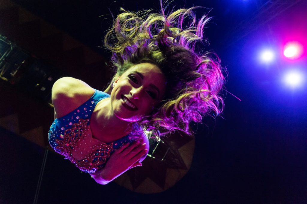 Circus artists swings from an aerial device. The camera angle is just below her. She has a big smile.