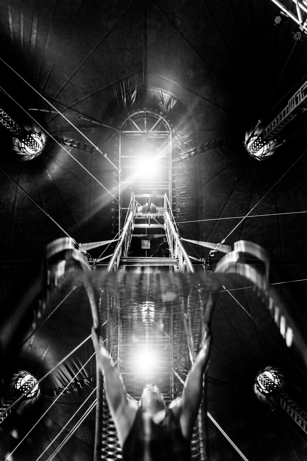 A man is holding on the the circus apparatus called the Wheel of Death. The camera angle is from underneath the device.