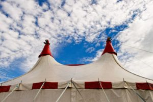 A big top circus tent with blue skies and pretty white clouds