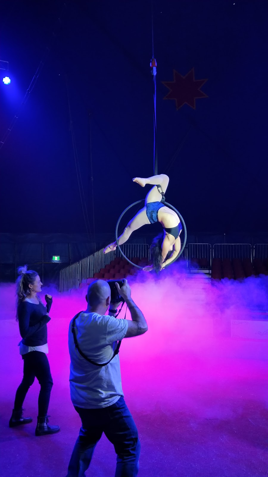 A photographer (with raised camera) and another person stand on a smoke filled stage looking at the lyra perfomer.