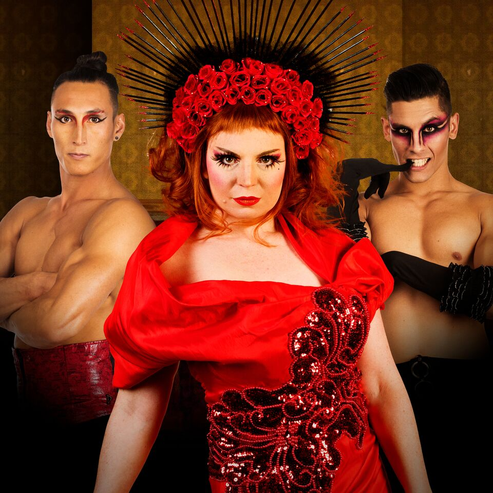 One woman dressed in a red dress and rose hat with radiating spikes is flanked by two shirtless men sporting red eye makeup.