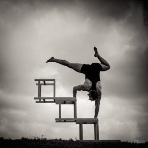 A man balances on three chairs that have been laid sideways and stacked. The sky is cloudy and dramatic behind him.