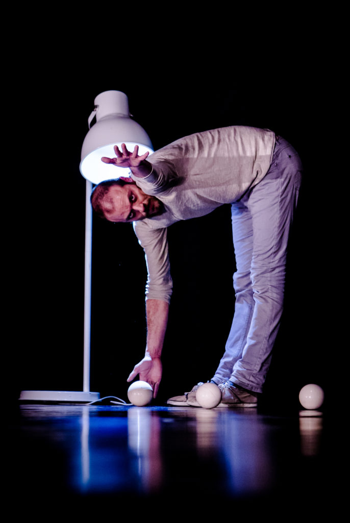 Man on stage picking up juggling balls