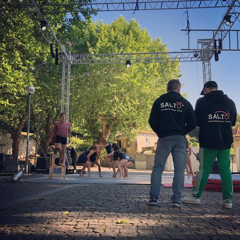 Circus instructors observe an outdoor rehearsal