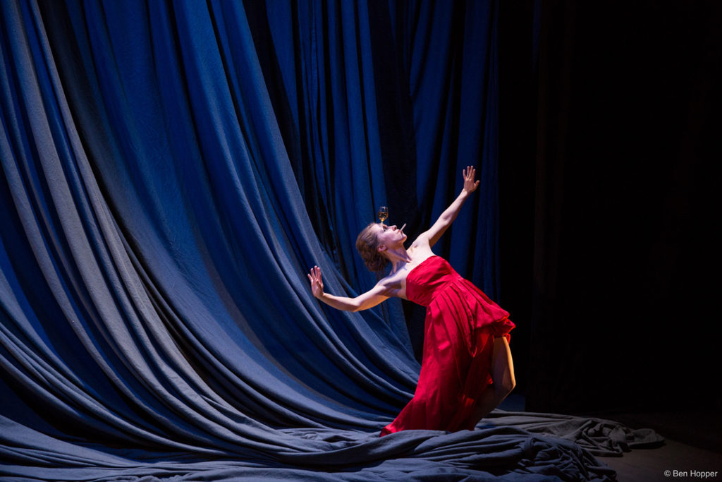 Woman in red dress standing on stage on draping silks gestures dramatically