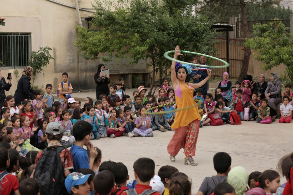 Woman hula hooping for a crowd of children in Lebanon