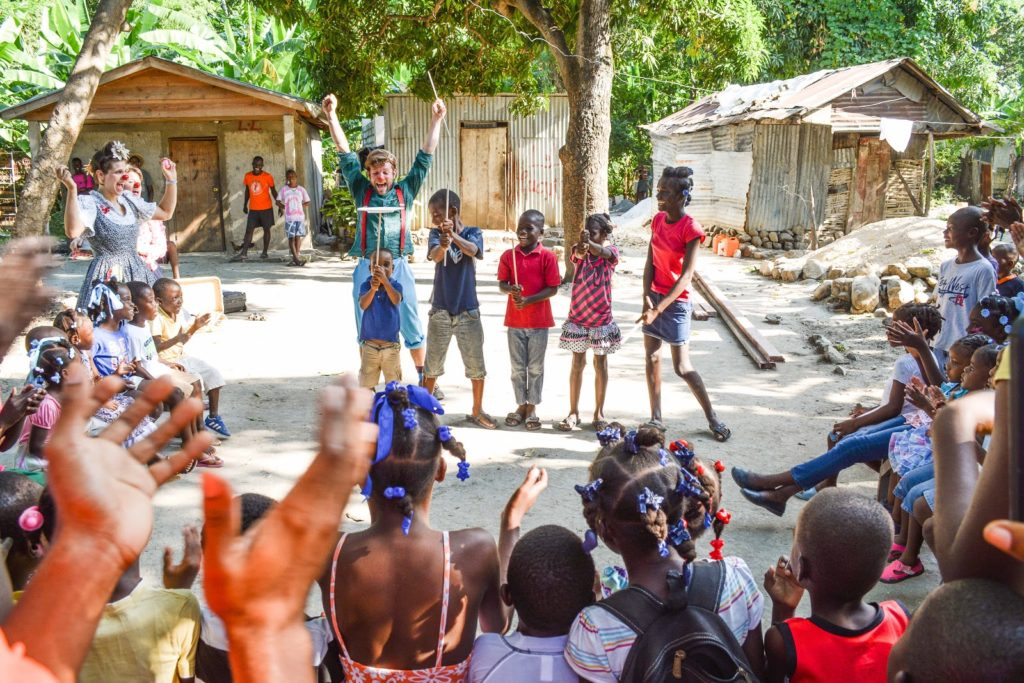 Children spinning plates with a clown in Haiti