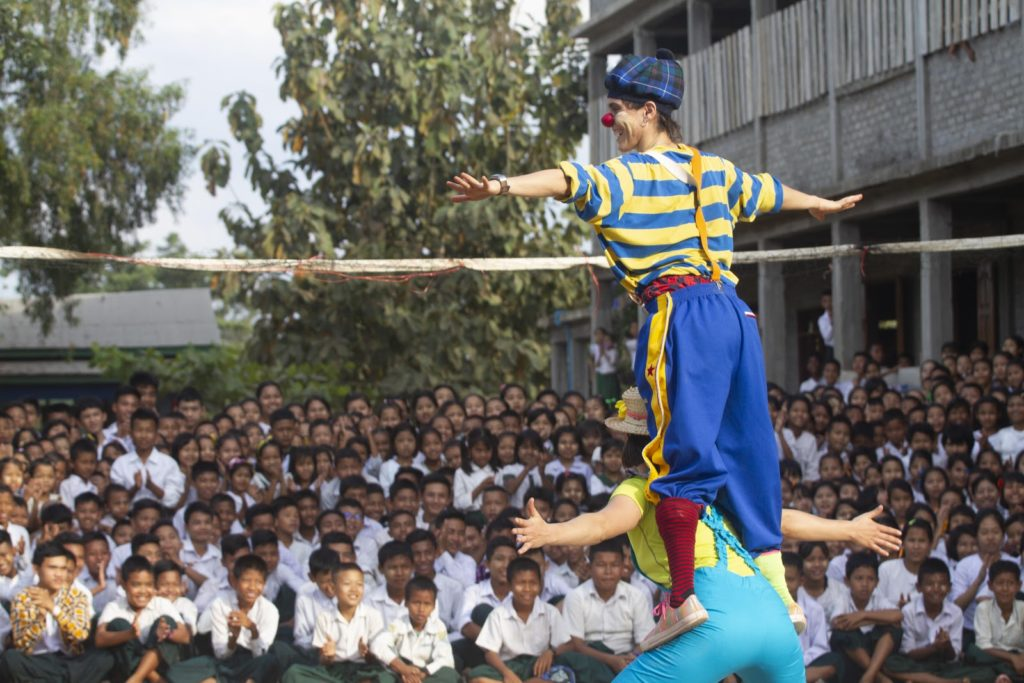 Clowns performing outside for a group of school children