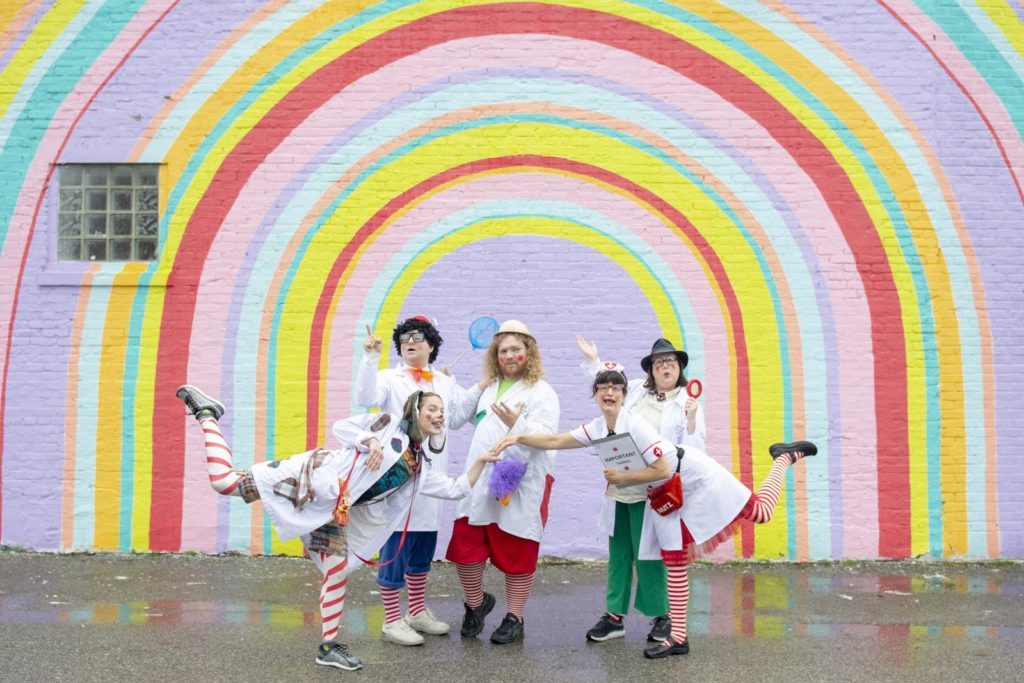 Doctor clowns posing together in front of a rainbow street art painting