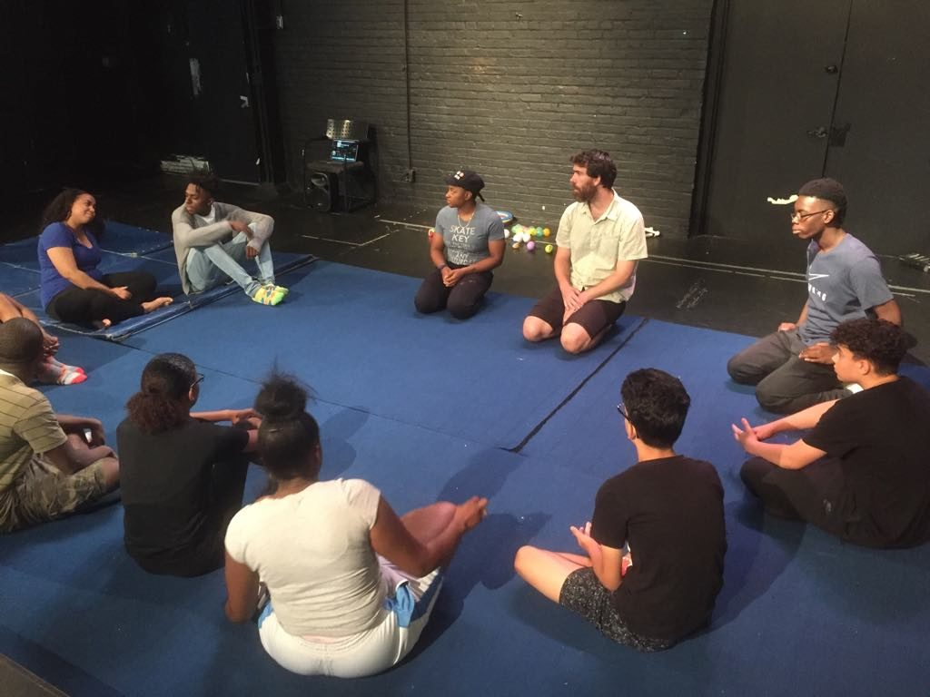 Circle of people sitting cross legged