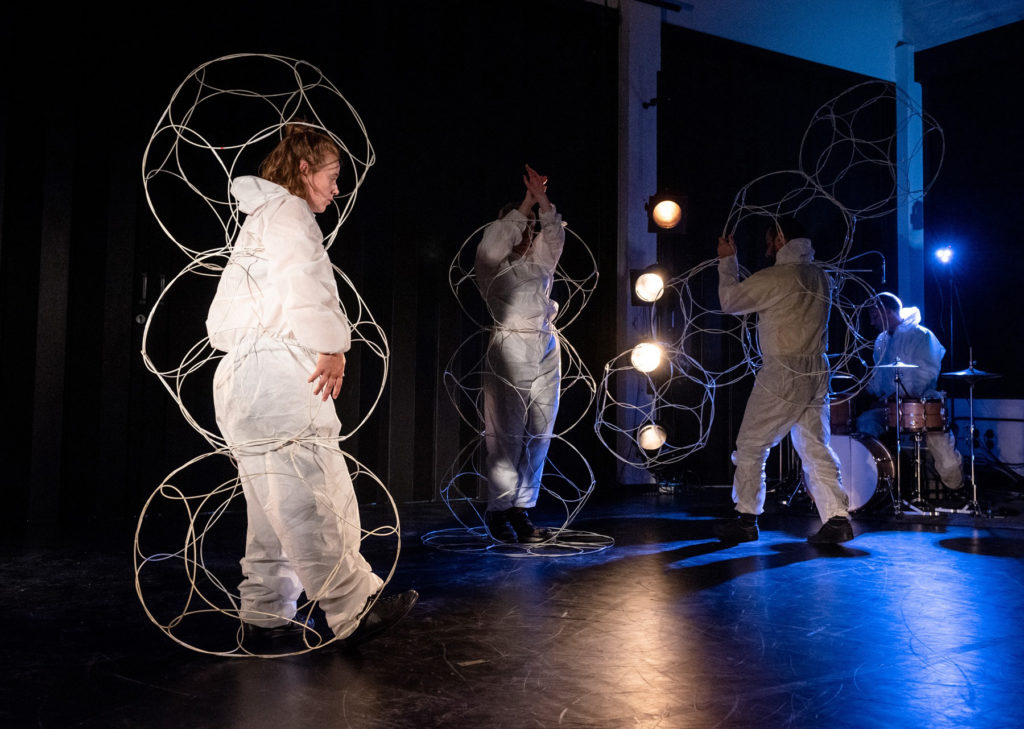 3 people in white pose inside of spherical wire structures