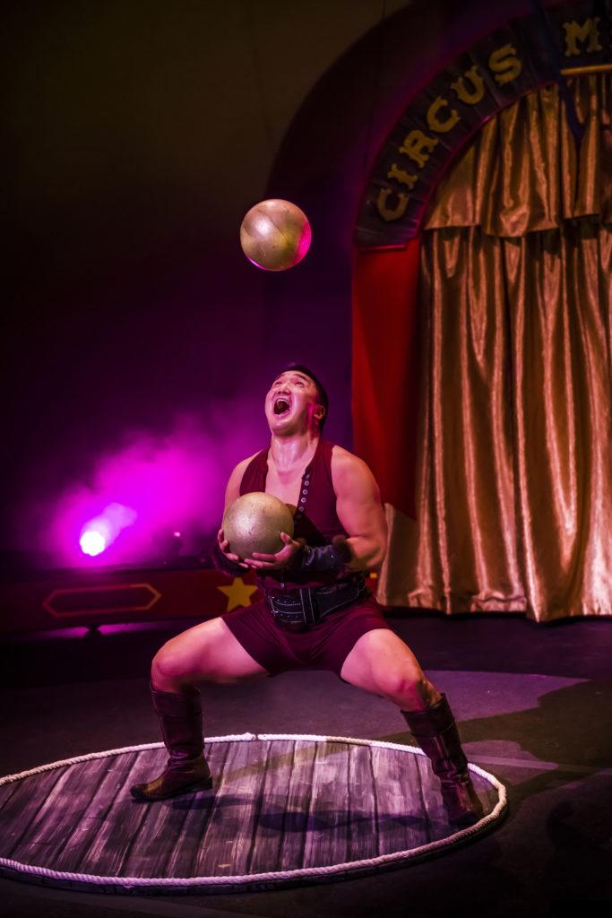 Strongman juggling bowling balls