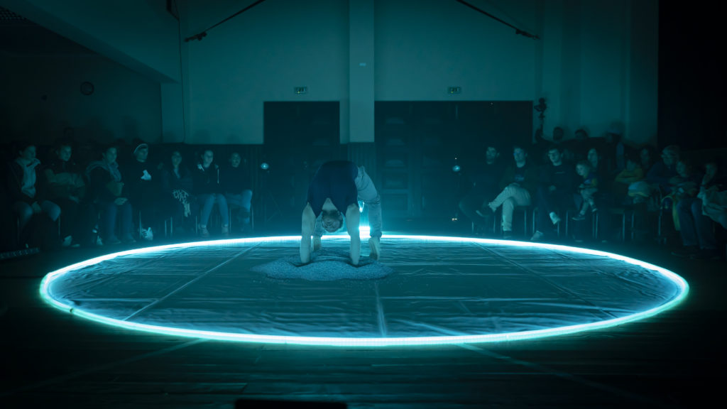 A circus performer in a ring lit with blue light