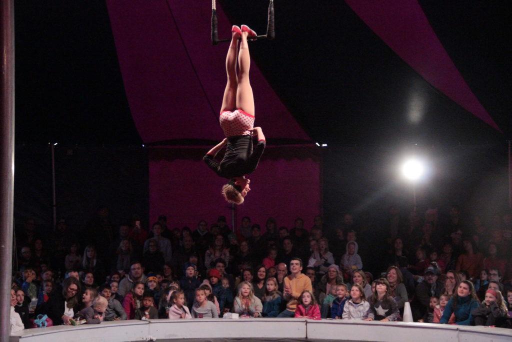 Woman on trapeze--toe hang