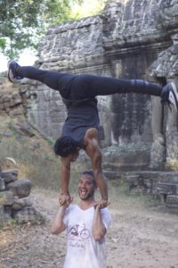 Director and circus artists goofing around on set with a hand balancing routine