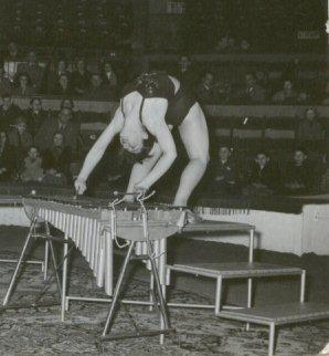 Black and white photo of circus artist contorting herself while playing a xylophone