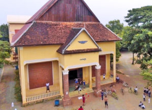Phare Ponleu Selpak in Cambodia. Shows an aerial view of a yellow building with a brown roof and students outside