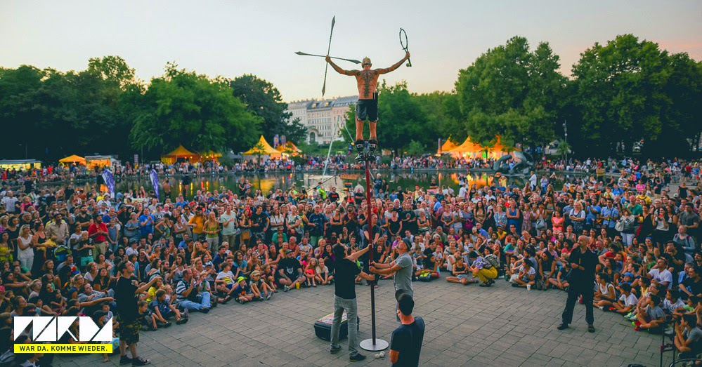 A street performer in Vienna stands high up on a pole in front of a large audience
