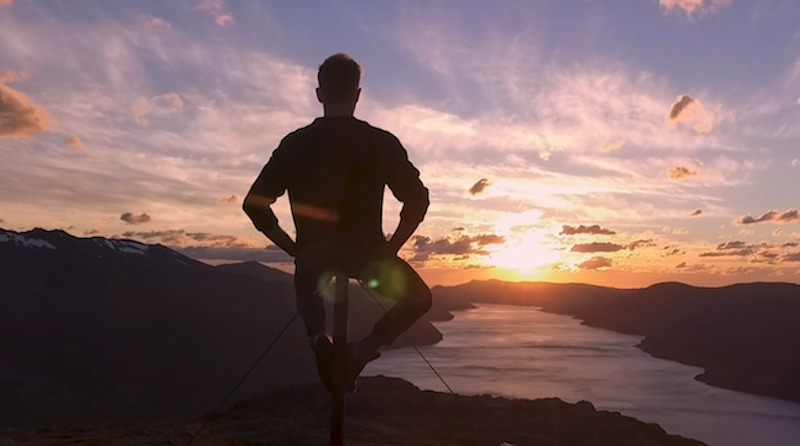 A man is silhouetted with his arms akimbo, sitting on the top of a pole, on the top of a mountain, overlooking a lake below, aglow in oranges and yellows of sunset