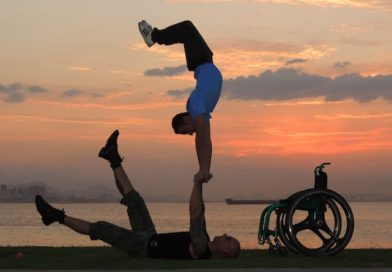 duo Dupla Mao Na Roda performing hand balancing by a lake at sunset. Photo description: There are bluish grey clouds and the sky is orange.Two handbalancers are silhoutted in the forefront. One hand balancer lays on the ground holding hands with the second hand balancer who is doing a handstand on the hands of the first. Also in the silhouette is the wheelchair of one of the handbalancers.