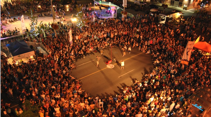 A large crowd gathers around a group of street performers