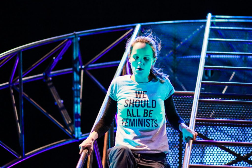 A white woman in her early thirties is climbing down the same steel structure. She is an aerialist and acrobat wearing a T shirt that says ' We should all be feminists'