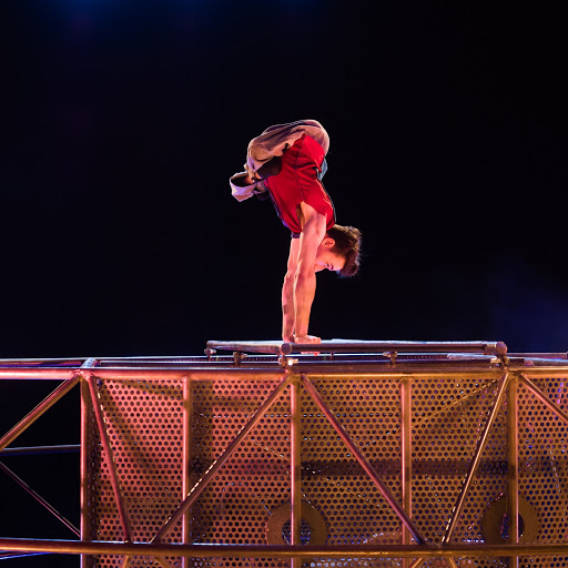 A acrobat who is disabled pushes his whole body skyward in a handstand.He is on the steel structure. The artist has legs that are folded neatly and tightly closely beneath his torso. He uses only his arms to weight bear.