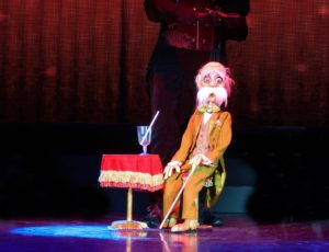 A puppet depicting an older man with a large comical mustache in a tweed suit with a cane sitting by a small table with a drink