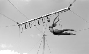 An aerialist performs a deep back bend on the lyra in black and white