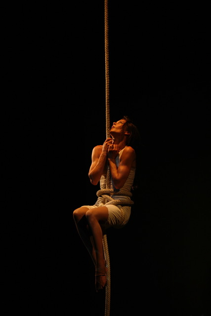 A performer assumes a seated hip key on the vertical rope