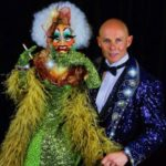 Murray Raine, wearing a sparkly purple tuxedo, holding up a large, elaborate humanoid puppet with a green showgirl dress and a painted face