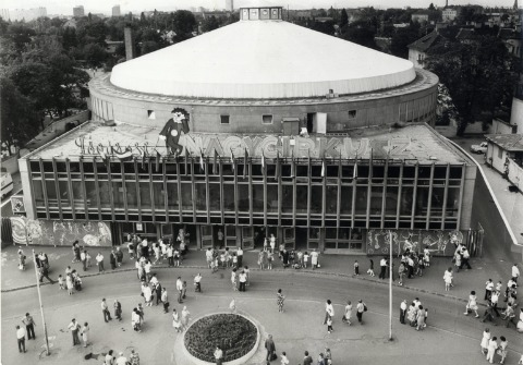 The new circus building in black and white with a crowd gathering outside