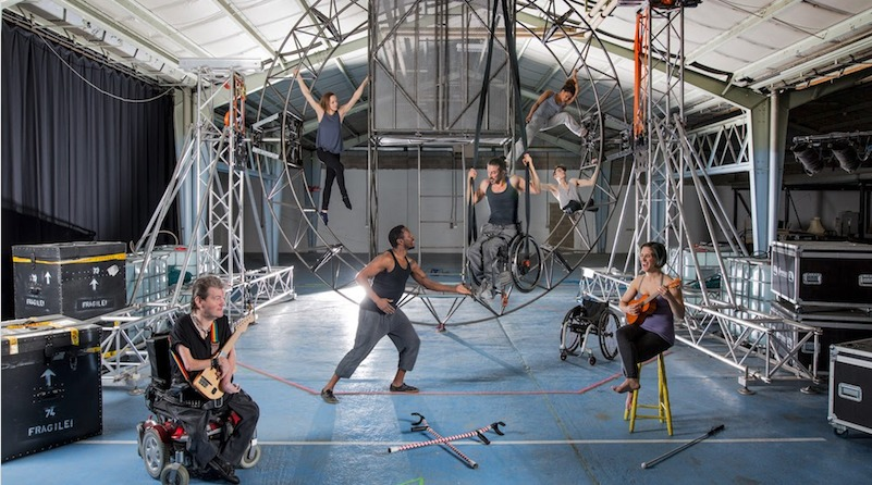 Seven performers disabled and non disabled surround a steel circular structure that they hang from . Two artists seated in front play stringed unique instruments. Crutches lay on the floor . An artist who is a wheelchair user is suspended in his wheelchair from the structure.