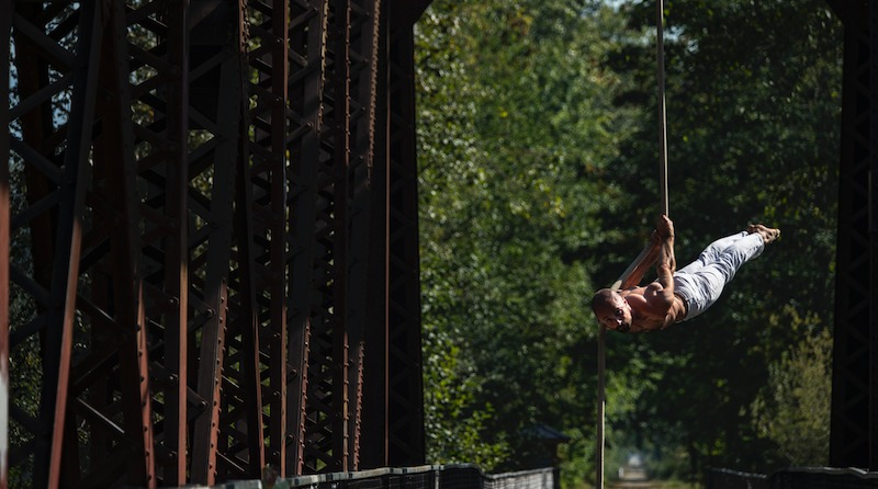 A man performs a back lever on aerial rope