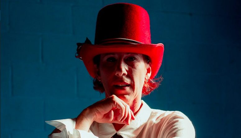 Aloysia Gavre staring into the camera thoughtfully, resting a hand on her chin, wearing a white button down and a large red hat
