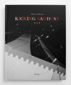Cover photo of Kicking Sawdust, depicting the top of a black and white tent from below