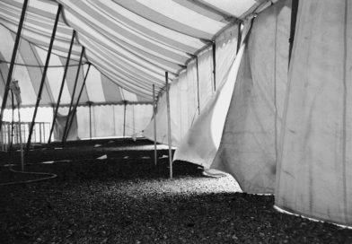 A black and white image of tent flaps held up my ratchet straps