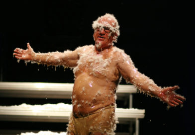 Professional clown Leo Bassi spreads his arms open while covered in honey and feathers