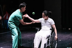 Two performers juggle on stage, one wearing scrubs, and another in a wheel chair