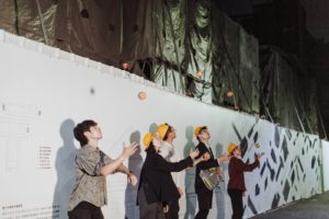 Jugglers toss yellow balls in front of a white wall