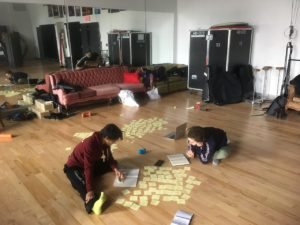 Two people sit on the floor surrounded by sticky notes and journals as they work on show ideas for Cirque Eloize