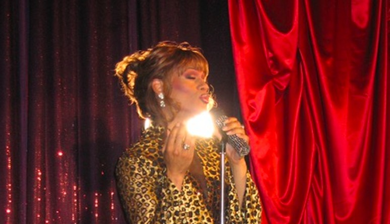 Ikenna stands on stage in costume, crooning into a microphone in front of a red velvet backdrop