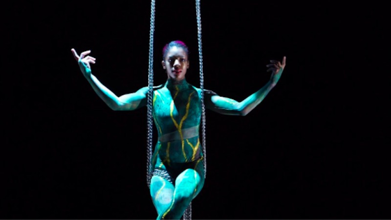 Aerialist Summer Lacy sits on the aerial chains wearing a green bodysuit
