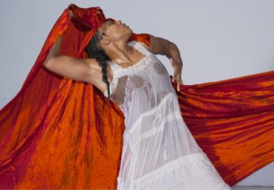 A Black woman wears a wet white gown, leaning back into a long crimson sash