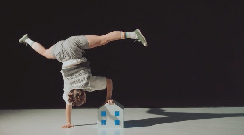 A handbalancer wearing a school uniform holds a one armed handstand, holding a small toy house and waving their legs
