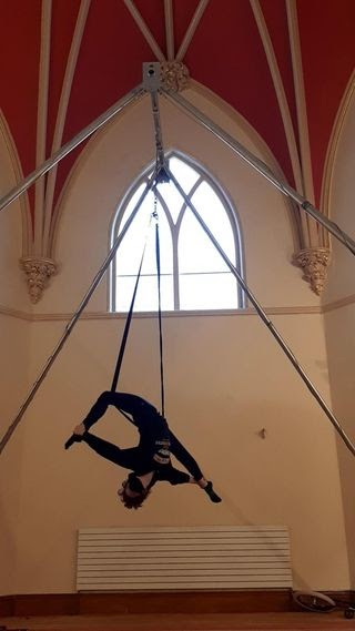 A circus artist hangs from a static trapeze in a split