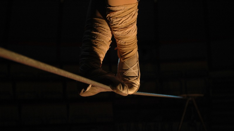 A tight wire is cast in shadow as two feet balance on top