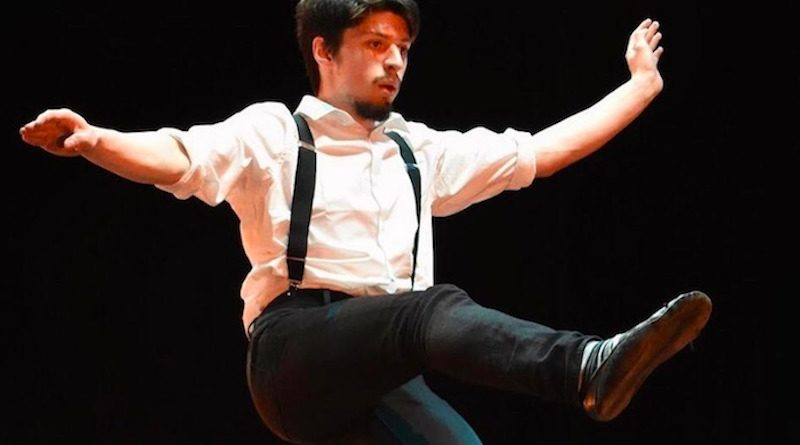 Finn Burnett-Pope balances on one leg on the tight wire wearing a white shirt and suspenders